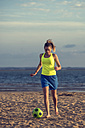 Spain, Young woman playing soccer at the beach - KIJF000084