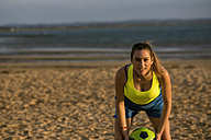 Spain, Young woman playing soccer at the beach - KIJF000087