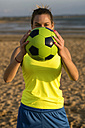Spain, Young woman playing soccer at the beach - KIJF000090