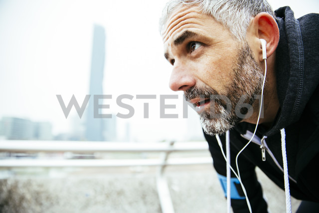 Austria, Vienna, exhausted athlete wearing earphones - AIF000156