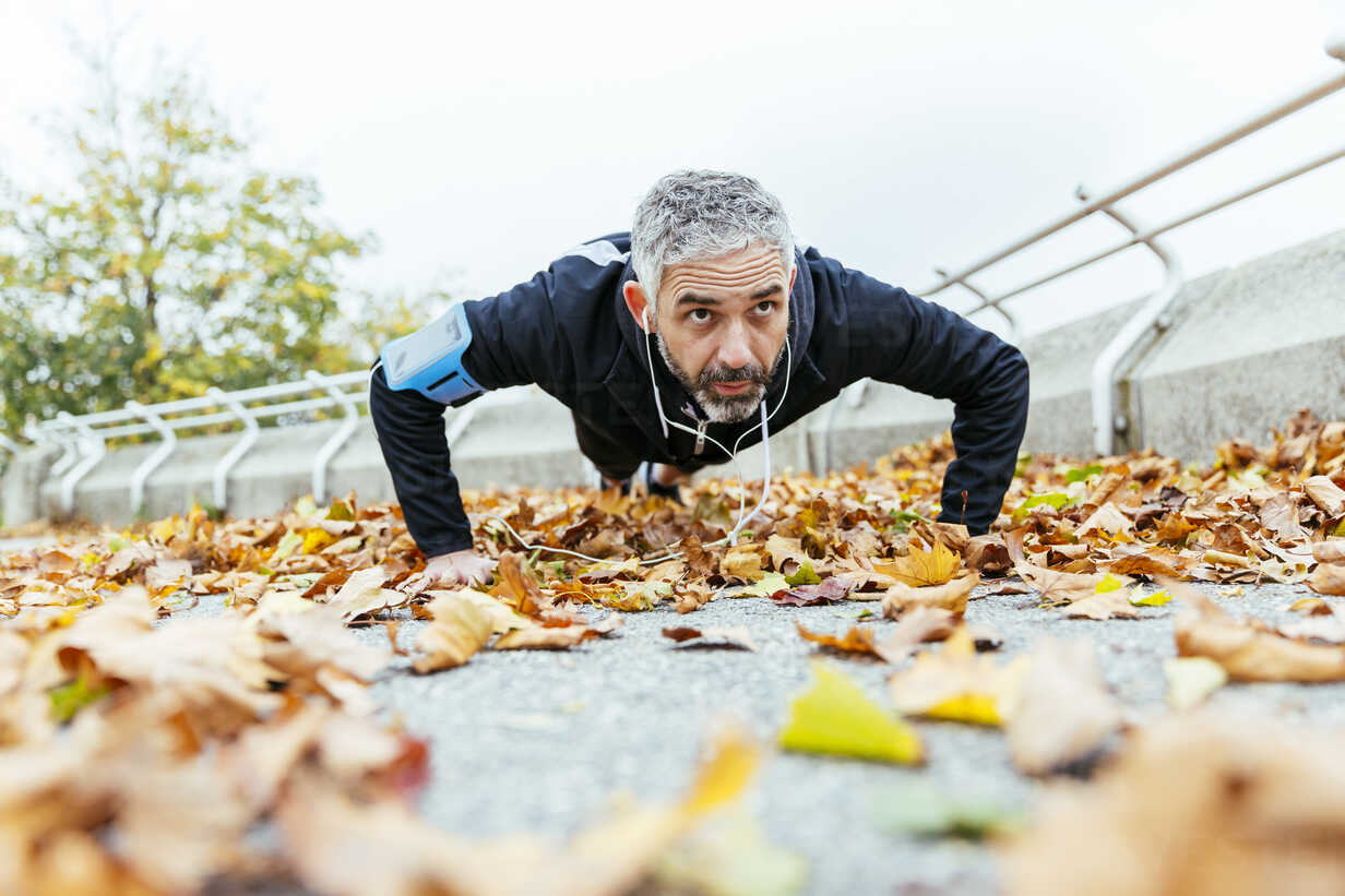 Man doing pushups surrounded by autumn leaves - AIF000162 - AustrianImages/Westend61