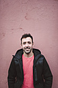 Portrait of smiling man with stubble standing in front of a wall - RAEF000762