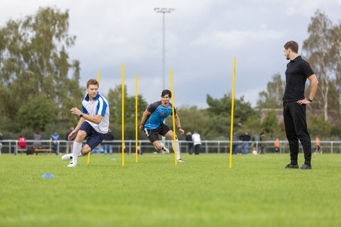 Coach exercising with soccer players on sports field - SHKF000387