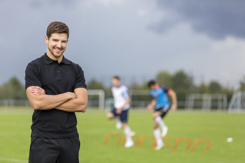 Portrait of smiling coach with soccer players in background - SHKF000393