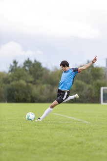 Soccer player kicking ball on sports field - SHKF000399