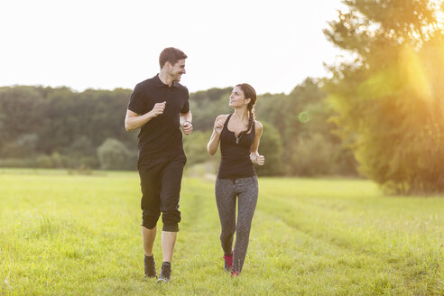 Man and woman jogging in field - SHKF000408