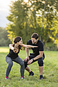 Man looking at woman doing knee bends in field - SHKF000414