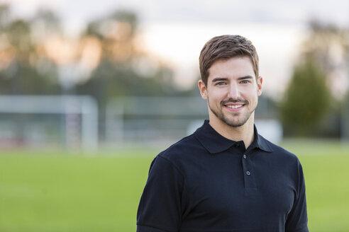 Portrait of smiling man on sports field - SHKF000420