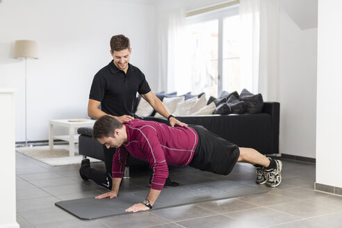 Coach doing exercises with man at home - SHKF000423