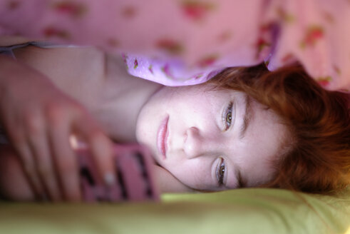 Portrait of girl lying under blanket in bed looking at her smartphone - LBF001335
