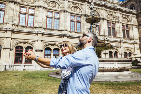 Austria, Vienna, smiling couple dancing Viennese waltz in front of state opera - AIF000167