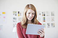 Young woman in office holding digital tablet - RBF003919