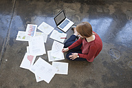 Young woman in office sitting on floor working through papers - RBF003937