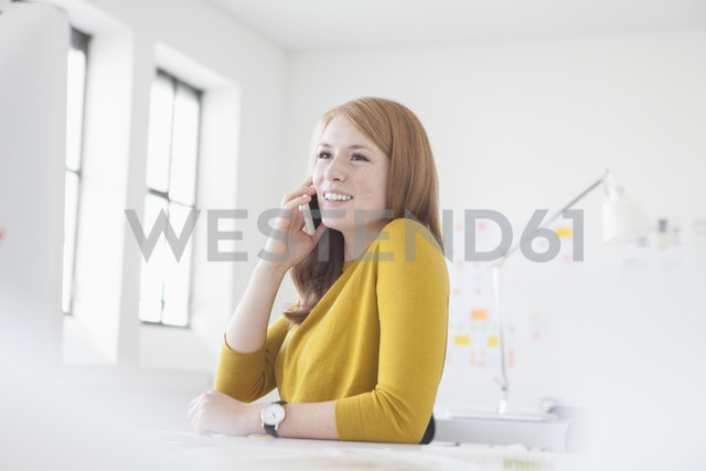 Young woman in office working at desk, using smart phone - RBF003940 - Rainer Berg/Westend61