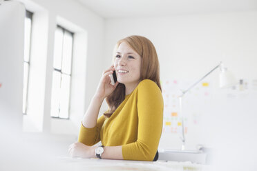 Young woman in office working at desk, using smart phone - RBF003940