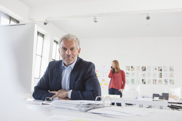 Businessman and coworker working in office - RBF003976