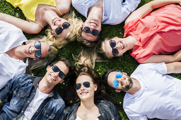 Happy friends wearing sunglasses lying in meadow together - DAWF000441