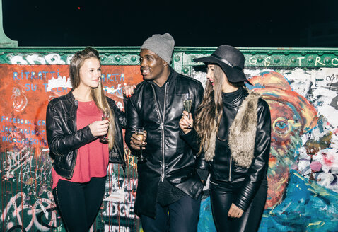 Friends holding champagne glasses standing at graffiti wall at night - OIP000059