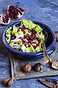 Bowl of Romaine lettuce with walnuts, pomegranate dressing and seed - SBDF002618