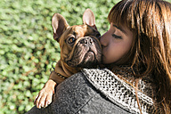 Portrait of young woman kissing French bulldog - GEMF000603