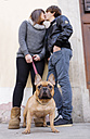 Portrait of French bulldog with owners kissing in the background - GEMF000609