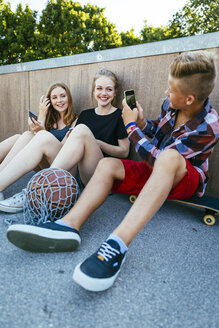 Teenage boy taking cell phone picture of friends outdoors - AIF000171
