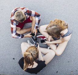 Three teenagers sitting outdoors with smartphones - AIF000183