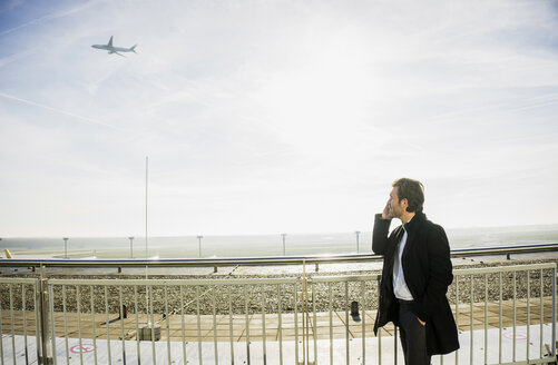 Germany, Frankfurt, Young businessman at the airport using smartphone - UUF006319