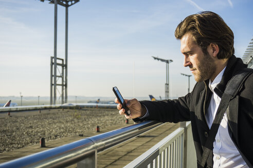 Germany, Frankfurt, Young businessman at the airport using smartphone - UUF006325