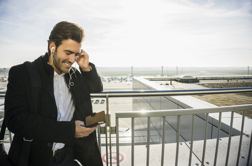 Germany, Frankfurt, Young businessman at the airport using smartphone - UUF006331