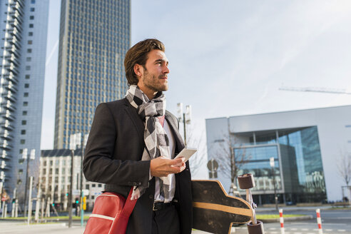 Germany, Frankfurt, Young businessman walking the city with skateboard, using mobile phone - UUF006334
