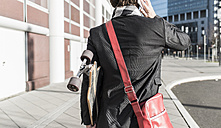 Germany, Frankfurt, Young businessman walking the city with skateboard, using mobile phone - UUF006337