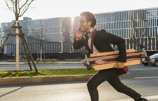 Germany, Frankfurt, Young businessman running with skateboard under his arm, using mobile phone - UUF006340