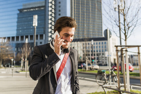Germany, Frankfurt, Young businessman walking the city using mobile phone - UUF006343