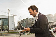 Germany, Frankfurt, Young businessman in the city with bicycle, using mobile phone - UUF006352