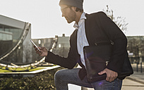 Germany, Frankfurt, Young businessman in the city using mobile phone - UUF006358