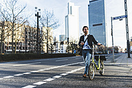 Germany, Frankfurt, Young businessman in the city with bicycle, using mobile phone - UUF006361