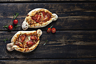 Two small pizzas, rosemary and cherry tomatoes on dark wood - CSF026955