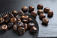 Fresh and roasted chestnuts on dark background - CSF026961