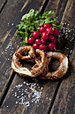 Two pretzels, red radishes and scattered salt grains on dark wood - CSF026988