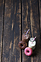 Two glass bottles of milk and cocoa and two doughnuts with different icings on dark wood - CSF027006