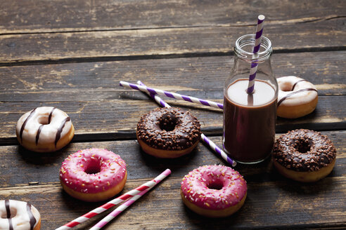Glass bottle cocoa, drinking straws  and doughnuts with different icings on dark wood - CSF027009