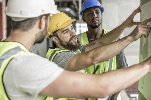 Construction workers discussing building plan in construction site - ZEF007842