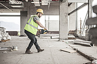 Construction worker using tape measure in construction site - ZEF007863