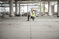 Construction worker using tape measure in construction site - ZEF007866