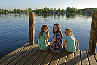 Germany, Mirow, three girls sitting on a jetty at Lake Mirow - LBF001342