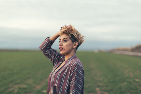 Portrait of woman with hand in her hair on a field - JPF000095
