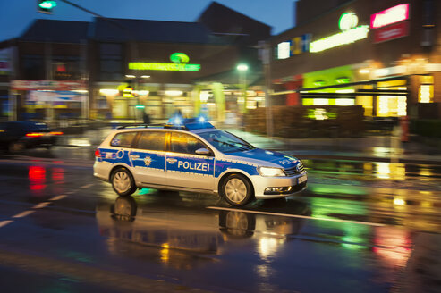 Germany, Grevenbroich, Police car on rainy street - FR000377
