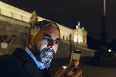 Austria, Vienna, portrait of man in front of parliament building looking at his smartphone by night - AIF000206