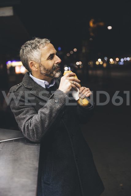 Austria, Vienna, man with Cheese Carniolan sausage at sausage booth by night - AIF000209